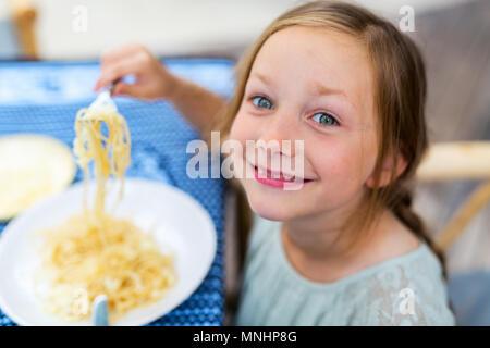 Portrait von entzückenden kleinen Mädchen isst Spaghetti für ein Mittagessen im Restaurant - Stockfoto