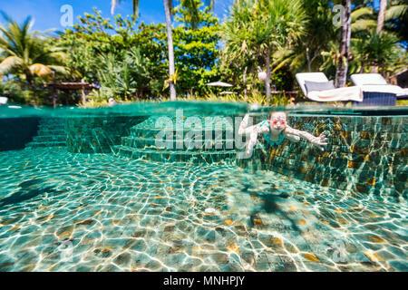 Split Unterwasser Foto der süßen kleinen Mädchen tauchen und schwimmen im Pool im Sommer Urlaub in Luxus Resort - Stockfoto