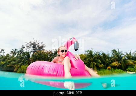Split Unterwasser Foto der süßen kleinen Mädchen mit rosa Flamingo aufblasbarer Ring schwimmen in einem tropischen Meer im Sommerurlaub - Stockfoto