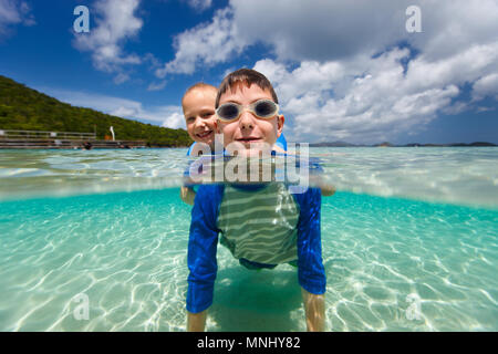 Split Unterwasser Foto der süßen kleinen Mädchen und niedlichen Jungen planschen in einem tropischen Meer Wasser in den Sommerferien - Stockfoto