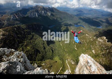 Hohe Betrachtungswinkel der Base Jumper im freien Fall direkt nach dem Sprung von hohen Felsen, New South Wales, Australien - Stockfoto