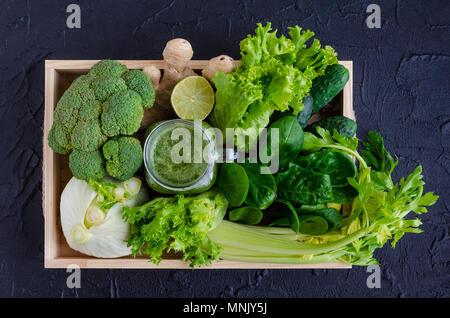 Detox gesunden grünen Smoothie in einem Marmeladenglas mit Zutaten: Spinat, Sellerie, Gurken, Salat, Ingwer, Fenchel, Kalk und Brokkoli auf ein Fach auf Schwarz - Stockfoto