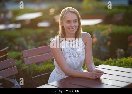 Eine charmante nachdenkliche junge Dame am Tisch sitzen auf der Terrasse im Freien. - Stockfoto