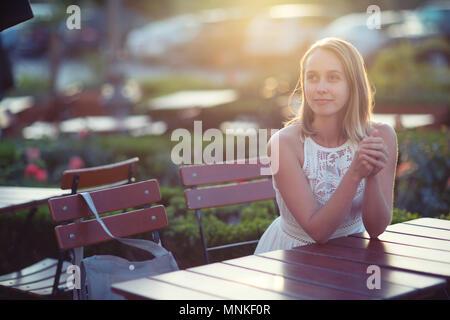 Schöne kaukasische Frau am Tisch sitzen - Stockfoto
