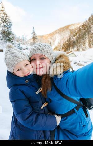 Mutter und Tochter unter selfie auf schönen Winter Tag im Freien. - Stockfoto
