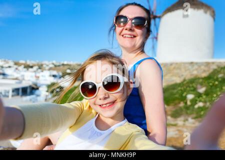 Glückliche Familie Mutter und ihre süßen kleinen Tochter auf den Urlaub nimmt selfie auf Klein Venedig Bereich auf der Insel Mykonos, Griechenland - Stockfoto