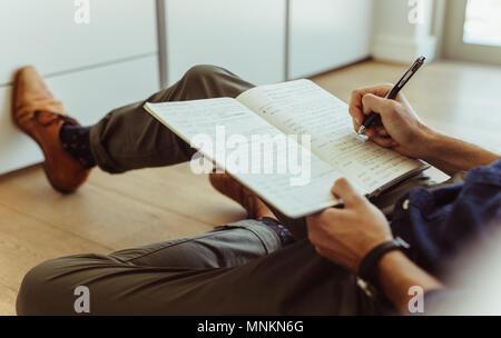 Seitenansicht der Mann sitzt der Etage zu Hause und Notizen in ein Tagebuch führen. Der Mann hält einen Stift und schreiben in Tagebuch. - Stockfoto