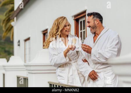 Schönes Paar in Bademantel klirren Gläser Wein und lächelnd. Freundliche Paar tragen Bademäntel mit Gläser Champagner in der Luxusvilla. - Stockfoto