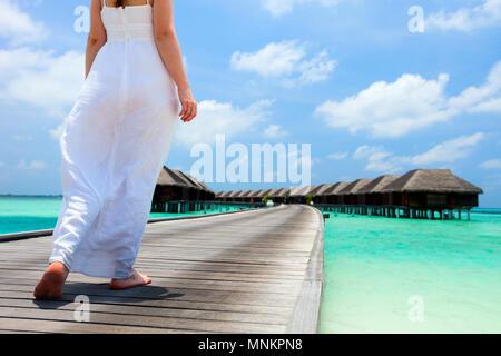 Schöne Mädchen in einem langen weißen Kleid auf einem Holzsteg Resort - Stockfoto