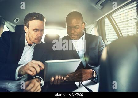 Zwei verschiedene Geschäftsleute mit einem digitalen Tablet beim zusammen auf dem Rücksitz eines Autos durch die Stadt fahren Sitzen - Stockfoto