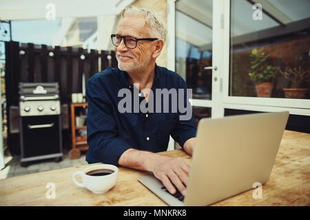 Lächelnd älterer Mann, trinken eine Tasse Kaffee und online arbeiten mit einem Notebook während an einem Tisch draußen auf der Terrasse sitzen - Stockfoto