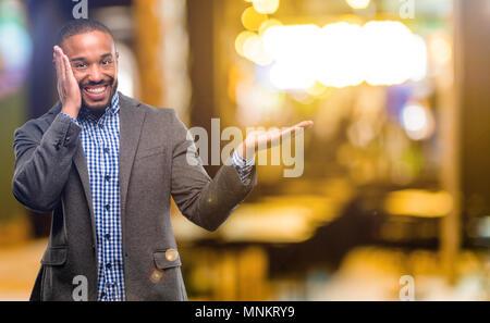 Afrikanische amerikanische Mann mit Bart halten etwas in leere Hand in der Nacht - Stockfoto