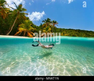 Frau Schwimmen unter Wasser in klaren tropischen Gewässern vor der exotischen Insel - Stockfoto