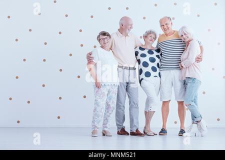 Gruppe der älteren Freunde umarmen einander in Weiß Studio mit Gold dots - Stockfoto