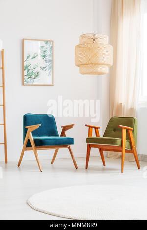 Handgefertigte Lampe über zwei Vintage Stühle in den hellen Raum mit Gemälden mit Blumenmotiv im weißen Wand - Stockfoto