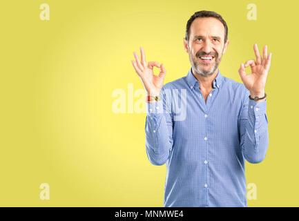 Gut aussehender Mann mittleren Alters zu tun ok Zeichen Geste mit beiden Händen zum Ausdruck zu Meditation und Entspannung - Stockfoto