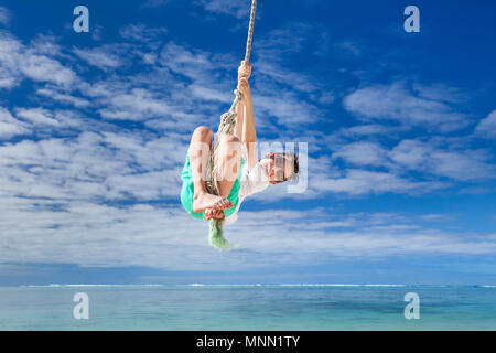 Cute boy Spaß Schwingen am Seil im Tropical Island Beach - Stockfoto