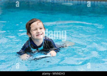 Junge spielt im Außenpool. Kinder üben Schwimmen mit Schaumstoff. - Stockfoto