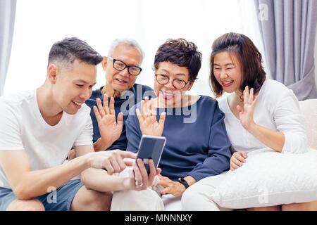 Erweiterte Familie Videoanruf und winkt für den Anrufer. Asiatische multi Generation Familie mit älteren und jungen Paar zusammen in glückliche Zeit - Stockfoto