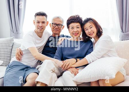 Asiatische Familie mit erwachsenen Kindern und älteren Eltern entspannt auf einem Sofa zu Hause zusammen - Stockfoto