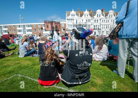 Wie Pearly Königinnen, eine Großmutter und Enkelin jubeln, während sie Prinz Harry und Meghan Markle Hochzeit auf einem großen Bildschirm an eine königliche Hochzeit Veranstaltung in Bexhill On Sea in East Sussex, England gekleidet. - Stockfoto
