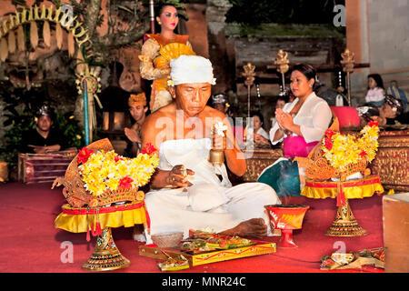 BALI - Januar 19: Legong Trance & Paradies Tanz in Ubud Palace. Vor der Leistung, Priester religiöse Zeremonie von Angeboten und segne alle akt - Stockfoto