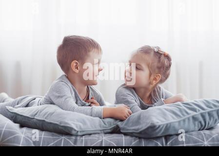 Kinder im Bett der Eltern. Kinder Aufwachen im sonnigen weißen Schlafzimmer. Junge und Mädchen spielen in der passenden Schlafanzug. Nachtwäsche und Bettwäsche für Kind und Baby. Baumschule Innenraum für Kleinkind Kind. Familie morgen - Stockfoto