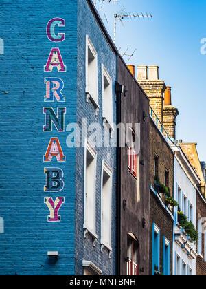 Carnaby Street London - gemalte Zeichen auf der Seite eines Gebäudes im Londoner Stadtteil Soho, Carnaby ist bekannt als das Herz im Swinging London der 60er Jahre - Stockfoto