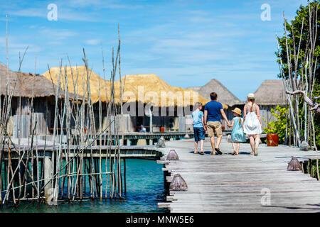 Rückansicht des gerne schöne Familie Wandern auf hölzernen Steg im Sommer Urlaub in Luxus Resort - Stockfoto