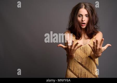 Junge schöne Frau gegen grauer Hintergrund - Stockfoto