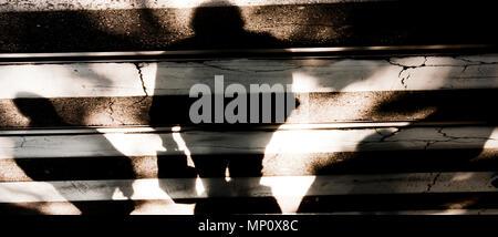Verschwommene Schatten Silhouette von Menschen zu Fuß die Straße der Stadt und der ältere Mann auf Zebrastreifen in sepia schwarz und weiß - Stockfoto