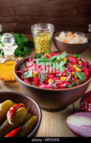 Vinaigrette Salat mit gekochtem Gemüse, Gewürzgurken, Sauerkraut und Konserven Erbsen in einem Ton Schüssel. Traditionelle russische Snack. Vegetarische fo - Stockfoto