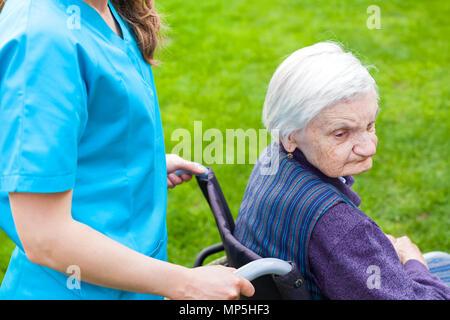 Ältere behinderte Frau im Rollstuhl wandern Outdoor mit weiblichen Hausmeister - Stockfoto