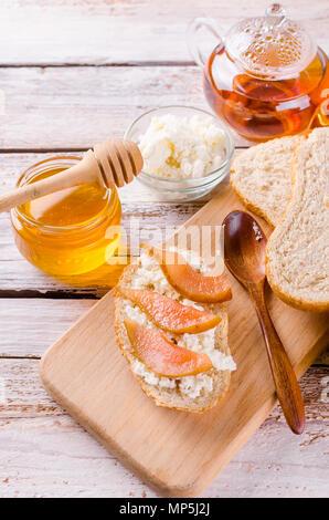 Frühstück. Tee mit Sandwiches mit ricotta Käse und pear Jam. Tasse Kaffee und Teekanne aus Glas. Ansicht von oben, kopieren Raum - Stockfoto