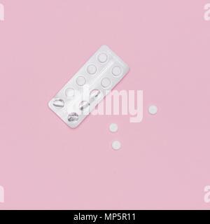 Weiße Pillen und Blisterpackung auf Rosa pastellfarbenen Hintergrund. Pharmazeutische Industrie minimal noch Leben flach Hintergrund. Opioid-Epidemie. Stockfoto
