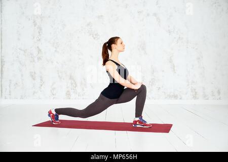 Aufwärmen vor dem Training. Junge schöne junge Frau in Sportkleidung zu tun Stretching. Fitness, Sport, Training und Personen Konzept. - Stockfoto