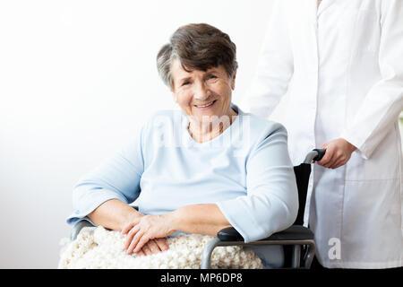 Lächelnd behinderte ältere Frau in einem Rollstuhl in der pflegeversicherung Haus - Stockfoto