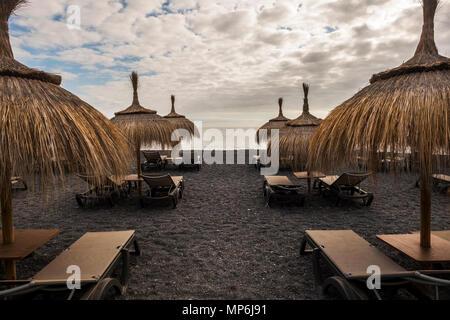 Sonnenschirme und Sitze am Strand in Insel Teneriffa. Platz für Ferien mit niemand dort. Geschlossene Zeit für schlechtes Wetter - Stockfoto
