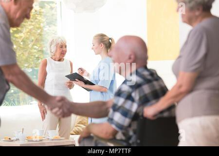 Ältere Frau im Gespräch mit einer Krankenschwester während der Sitzung im Wohnzimmer von Rest House - Stockfoto