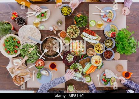 Freunde in gesunde vegetarische Mittagessen, sitzen an Holz Tisch - Stockfoto