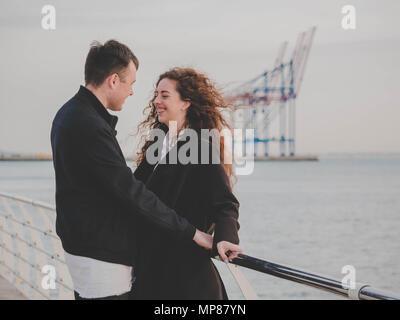 Junge romantische Paar in modischen Verschleiß am Datum, genießen Moment der Nähe am Meer oder Ozean Hintergrund. Frau mit lockigem Haar lächelnd zu ihr Mann. Roman - Stockfoto