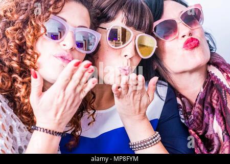 Drei kaukasischen Jungen lustig verrückte Frau tun, eine Partei mit bunten Sonnenbrillen. Senden Kuss und Spaß zusammen, die in einer echten Freundschaft. Gruppe Menschen ein