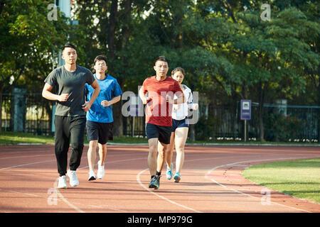 Vier jungen asiatischen Erwachsene Lauftraining auf der Strecke. - Stockfoto