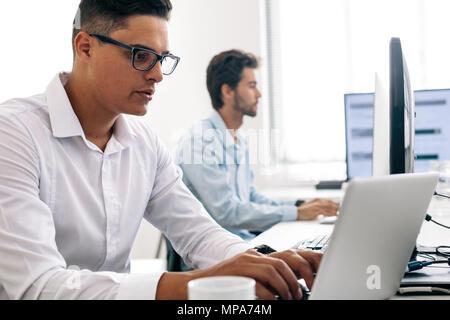 Software Entwickler im Büro sitzen, Arbeiten am Computer. Mann mit Brille arbeiten am Laptop im Büro. - Stockfoto