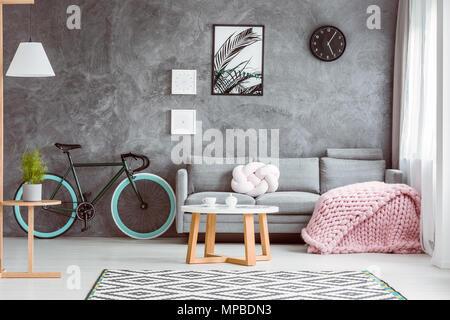Fahrrad mit Blue Wheels im gemütlichen Wohnzimmer mit Rosa gestrickte Decke und Kissen auf grau Sofa - Stockfoto