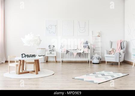 Rosa Decke auf grauen Sessel in Pastelltönen Kinderzimmer mit kleinem Tisch und Plüsch Spielzeug auf weißen Schrank - Stockfoto