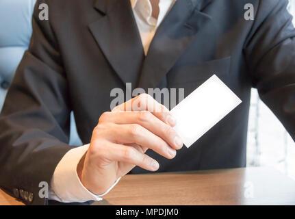 Mann in Anzug auf Tabelle mit leeren weißen Visitenkarte mockup Sitzen - Stockfoto
