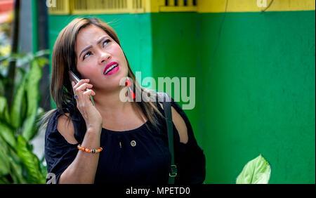 Eine attraktive Filipino asiatische Frau sieht nach oben, in der Kontemplation, während Sie Ihr Handy in den Philippinen. - Stockfoto