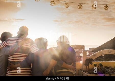 Gruppe 4 Personen älterer Erwachsener im Alter von Hug und zusammen auf der Dachterrasse in der Sonne Sonnenuntergang mit Hintergrundbeleuchtung und goldenen Farben auf der Suche bleiben. Ferienhäuser Konzept - Stockfoto