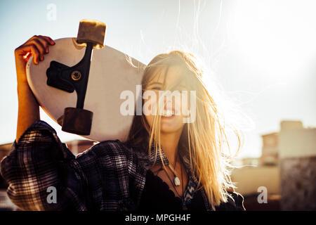 Schön caucasiamo blonde Modell freie Frau mit einem Skateboard in der Sonne Hintergrundbeleuchtung bei Sonnenuntergang. Freiheit und Unabhängigkeit Jugend Konzept auf Teneriffa. Hair